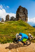 Tourist cycling in Cortina d'Ampezzo, stunning view of Cinque Torri and Tofana in background. Man riding MTB enduro flow trail. South Tyrol province of Italy, Dolomites. poster