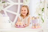 Little pleasured blond girl holding a pink plate looking on sweet cakes on the background of pretty decorated candy bar poster