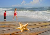 Starfish on boardwalk with kids playing by rolling ocean surf on pretty beach with puffy cloudscape in distance poster