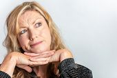 Studio portrait headshot of attractive thoughtful middle aged blond woman in her forties looking up inquisitive or questioning poster