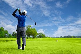 Man Playing Golf On A Golf Course In The Sun, Golfers Hit Sweeping Golf Course In The Summer