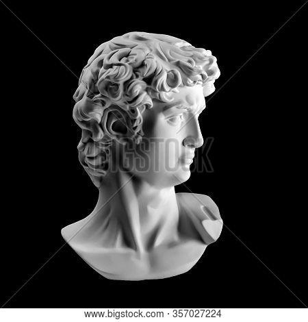 Gypsum Statue Of Davids Head. Michelangelos David Statue Plaster Copy Isolated On Black Background.