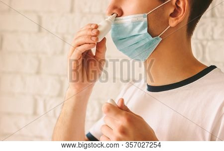Closeup Of Young Man With Sickness Using Nasal Spray For His Congested Nose. Confident Ill Doctor In