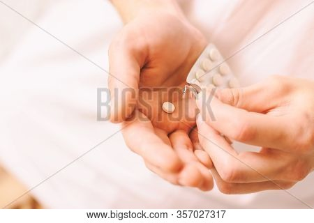 Closeup Of Man Hands With Plate Of White Round Pills. Sick Man Taking Oral Medications For Treatment