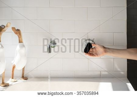 Cropped View Of Woman Hand Open Built In Chrome Water Tap To Fill Bathtub. Wooden Decor Standing On