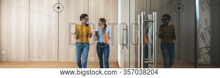 Two Young Coworkers Meeting While They Go Around Office Hall. Group Of Young Business People Meet An