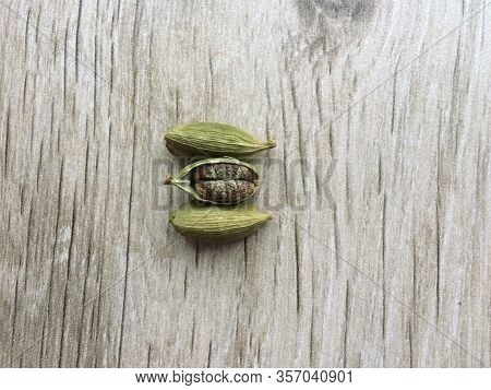 Top View Of Dried Green Cardamom Pod And Seeds Isolated On Wooden Background. Close Up.