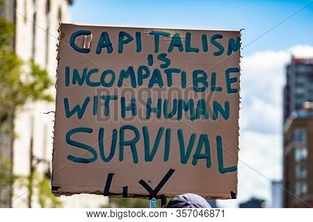 A Close Up Shot Of A Cardboard Sign Saying Capitalism Is Incompatible With Human Survival, As Enviro