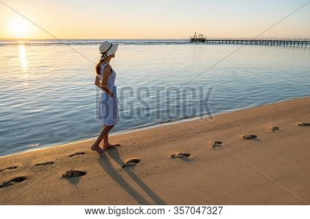 Young Woman In Straw Hat And A Dress Walking Alone On Empty Sand Beach At Sunset Sea Shore. Lonely G