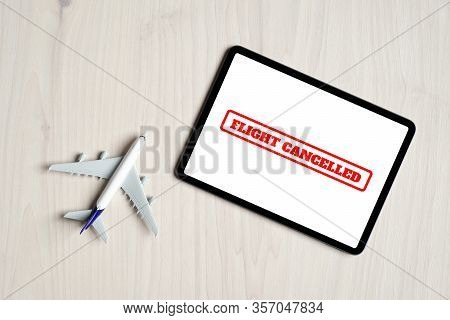 Flight Cancellations Concept. Top View Airplane Toy And Digital Tablet With Message