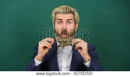 Being Open To Surprise In Classroom. Surprised Teacher Green Chalkboard. Bearded Man Look Surprised.