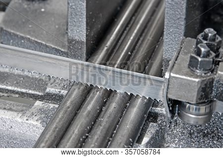 Automatic Band Saw With Coolant Liquid Cuts The Metal Rods Of The Workpiece, Industrial Band Saw For