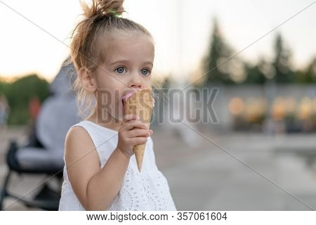 Little Caucasian Girl 3 Years Old Eats Ice Cream Closeup Portrait. Summertime. Childhood Child With