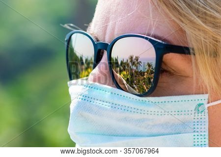 Travel And Healthcare Concept. Woman Wearing Medicine Mask And Sun Glasses With Tropical Resort Refl