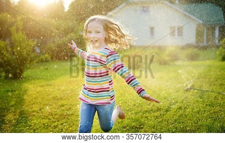 Adorable Girl Playing With A Sprinkler In A Backyard On Sunny Summer Day. Cute Child Having Fun With