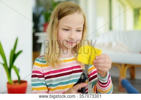 Young Girl Cutting Colorful Paper With Scissors At Home. Creative Kid Doing Crafts. Education And Di
