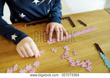 Close-up On Child's Hands Playing Puzzles At Home. Child Connecting Jigsaw Puzzle Pieces In A Living