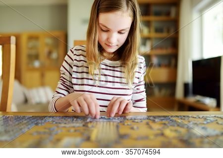 Cute Young Girl Playing Puzzles At Home. Child Connecting Jigsaw Puzzle Pieces In A Living Room Tabl