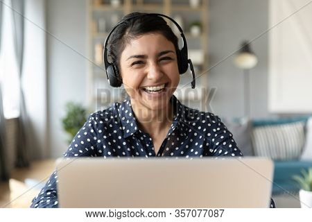 Head Shot Portrait Smiling Indian Woman Wearing Headphones At Workplace