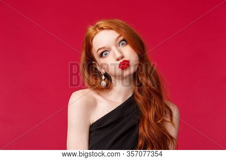 Close-up Portrait Of Silly And Funny Pretty Redhead Woman In Red Lipstick, Makeup And Black Evening