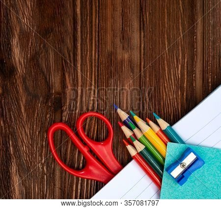 Colored Pencils, Sharpener, Scissors And Sheets For Notes In An Open Notebook On A Dark Brown Wooden