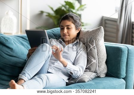 Peaceful Indian Woman Using Computer Tablet, Relaxing On Couch