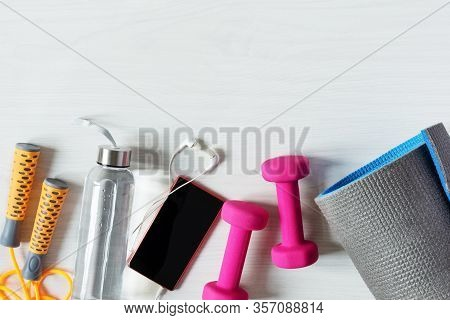 Fitness Equipment Top View With Copy Space. Fitness Concept. Dumbbells, Jump Rope, Water Bottle And