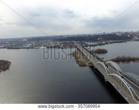 Aerial top view of automobile and railroad bridge across Dnepr river from above, Kiev city skyline, Ukraine