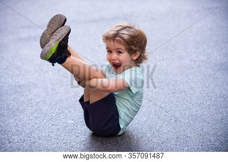 Happy Funny Child. Cute Kid Sits On The Pavement. Happy Child Portrait. Childhood On The Asphalt Roa