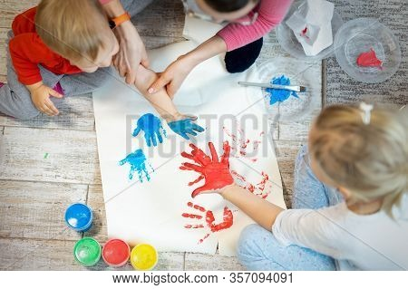 Adorable Cute Caucasian Little Blond Siblings Children Enjoy Having Fun Together With Mother Paintin