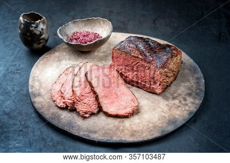 Traditional Commonwealth Sunday roast with sliced cold cuts roast beef with red salt as closeup on a modern design plate