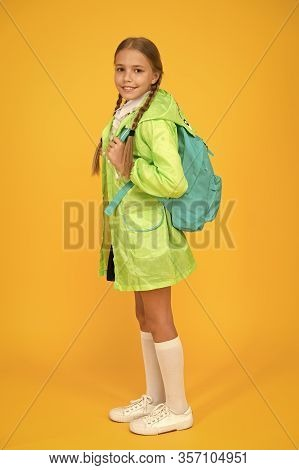 On Your Back And Ready To Go To School. Little School Girl Wear Cute Raincoat On Yellow Background.