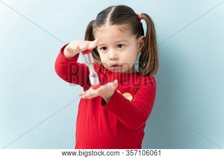Portrait Of A Beautiful Caucasian Girl Holding A Sand Timer And Practicing Self Control In A Studio