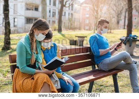 People sitting on park bench in the sun practicing social distancing in corona crisis wearing masks