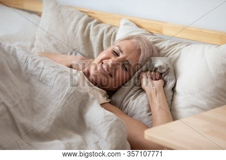 Smiling Middle Aged Retired Woman Waking Up In Cozy Bed.