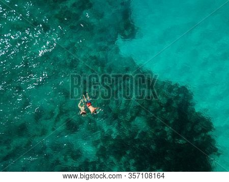 Snorkeling Couple In The Middle Of The Indian Ocean, Coral Reefs, Green Water, From High Above. Bird