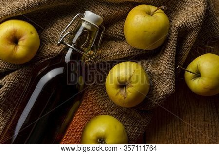 Full Bottle Of Cider With Basket Of Yellow Apples.