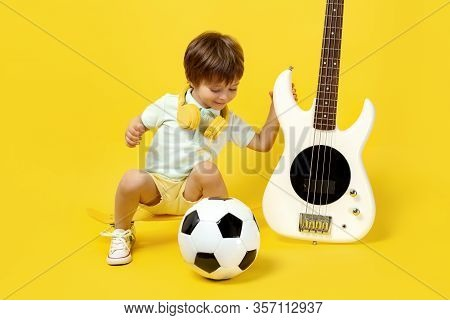 Cute Kid Sitting On Pennyboard With White Electric Bass Guitar, Soccer Ball And Headphone Over Yello