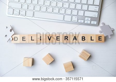 Modern Business Buzzword - Deliverable. Top View On Keyboard And Puzzle With Wooden Blocks. Close Up