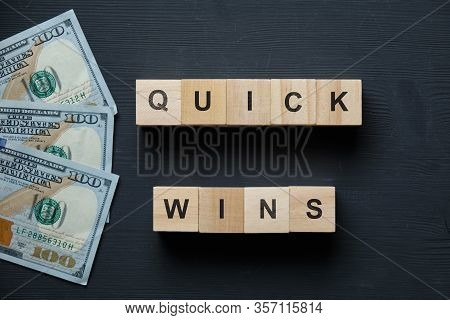 Modern Business Buzzword - Quick Wins. Top View On A Black Board With Dollars And Wooden Blocks. Clo