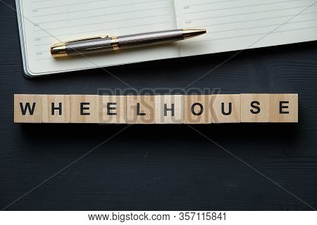 Modern Business Buzzword - Wheelhouse. Top View Oon A Black Board With Pen And Notebook, Wooden Bloc