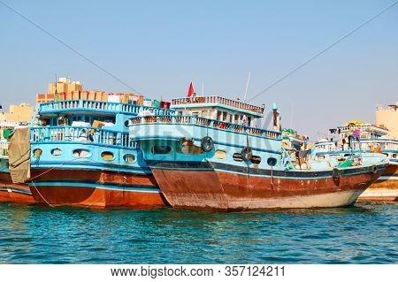 Dubai, UAE - January 31, 2020: Traditional arabian Dhow boats at the wharf in Deira in Dubai, United Arab Emirates