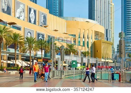 Dubai, UAE - February 01, 2020: Promenade around the Dubai Fountain near the Dubai Mall with walking tourists,  United Arab Emirates