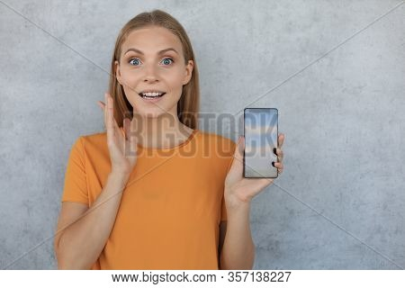 Portrait Of A Smiling Young Woman Showing Blank Screen Mobile Phone Isolated Over Grey Background