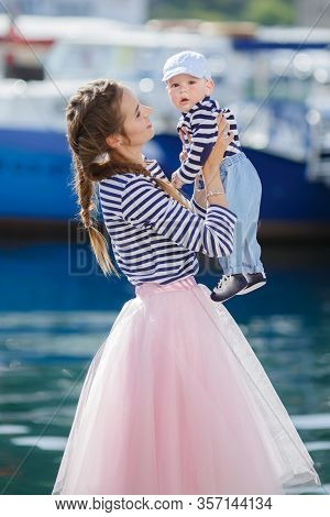 Mom And Son Are Sitting On The Old Pier And Enjoying The Sea.happy Mother And Baby In Striped Navy T