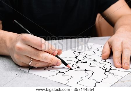 Man Is Drawing An Abstract Imaginary Picture Of Curves By A Black Pencil In His Hand. A Psychologica