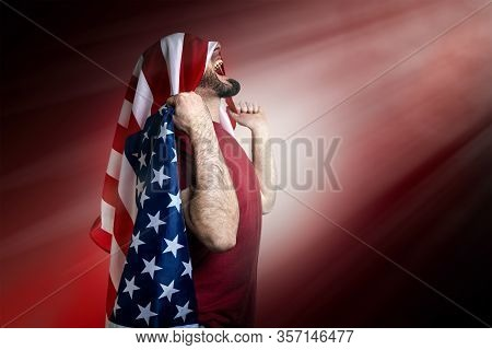 Caucasian Man With An American Flag On His Head Throws His Hands Up And Shouts. Dark Red Background