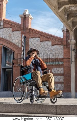 Young Paralyzed Man In A Wheelchair Frustrated In Front Of Some Stairs