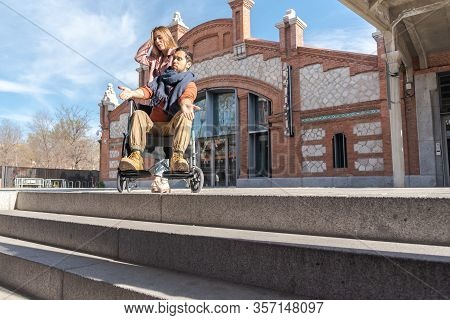 Young Paralyzed Man With Girl In A Wheelchair Frustrated In Front Of Some Stairs