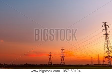 High Voltage Electric Pylon And Electrical Wire With Sunset Sky. Electricity Poles. Power And Energy